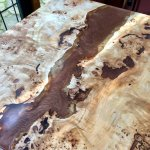 wood and resin dining table with shimmering chocolate river